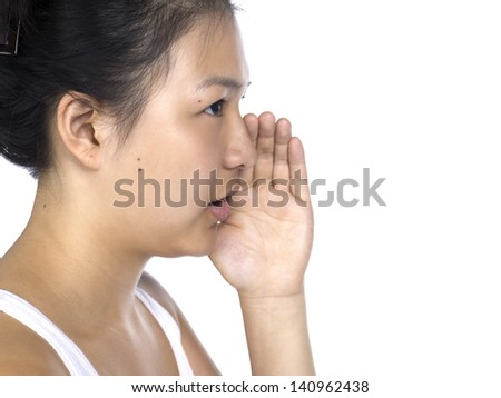 Side view of a young Asian woman whispering while standing against white background - stock photo