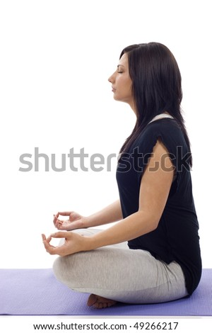 Side view of a young attractive woman in yoga lotus pose isolated on white background