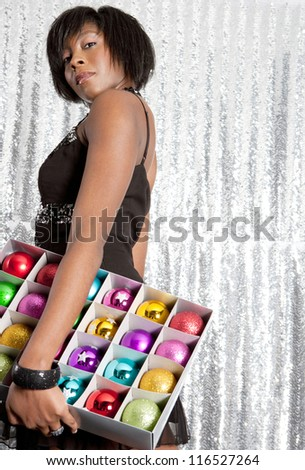 Side view of a young black woman holding a box with different color christmas balls decorations against a silver sequins background. - stock photo