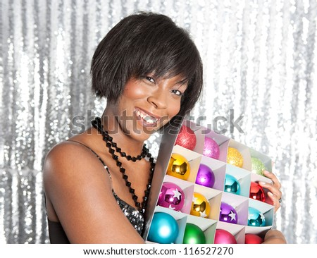 Side view of a young black woman holding a box with different color christmas balls decorations while smiling against a silver sequins background. - stock photo