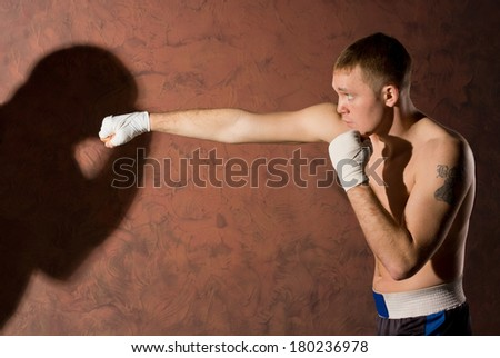 Side view of a young boxer punching his opponent with his arm extended towards the shadow of his competitor on the brown wall alongside, conceptual image - stock photo