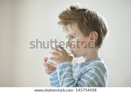 Side view of a young boy drinking milk - stock photo