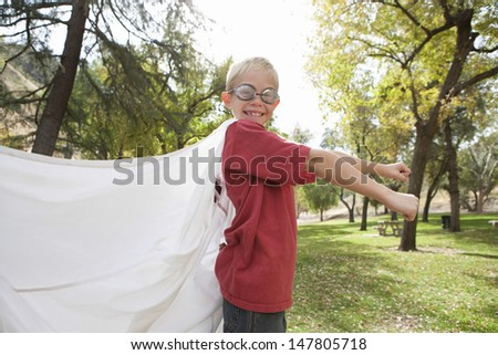 Side view of a young boy wearing cape and swimming goggles outdoors - stock photo