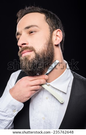 Side view of a young brutal bearded man with straight razor. Black background.