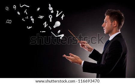 Side view of a young business man directing with a conductor's baton a bunch of symbols - stock photo