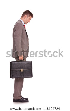 side view of a young business man holding a briefcase and looking down - full body picture - stock photo