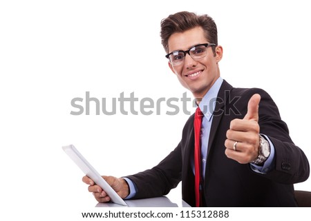 side view of a young business man holding a tablet pad and making the ok thumbs up gesture at his desk