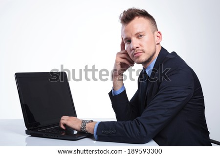 side view of a young business man sitting at his laptop and looking into the camera . on a gray studio backgroud