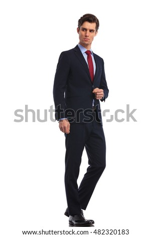 side view of a young business man standing and looks away from the camera on white background