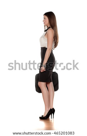 side view of a young business woman in a skirt with a bag