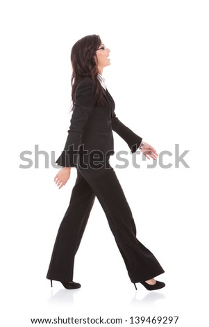 side view of a young business woman walking forward and laughing. on white background
