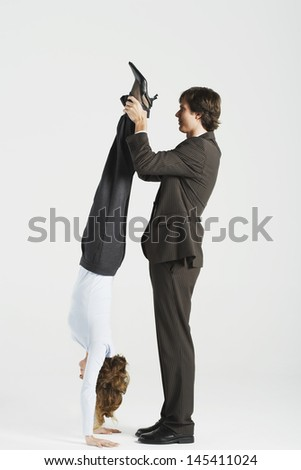 Side view of a young businessman holding legs of female colleague standing on hands against white background - stock photo