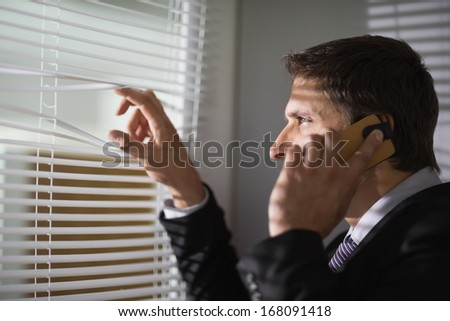 Side view of a young businessman peeking through blinds while on call in the office - stock photo
