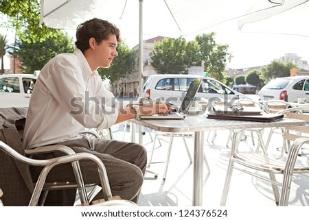 Side view of a young businessman using a laptop computer while sitting outdoors at a coffee shop terrace.