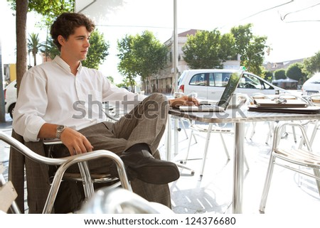 Side view of a young businessman using a laptop computer while sitting outdoors at a coffee shop terrace. - stock photo