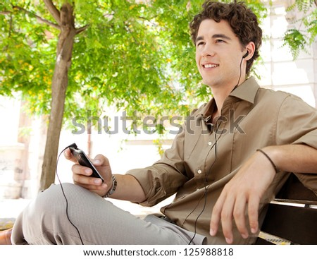 Side view of a young businessman using his smart phone and a hands free set while sitting on a bench in a city park, smiling.