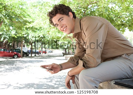 Side view of a young businessman using his smart phone while sitting on a ben in a city park, outdoors. - stock photo