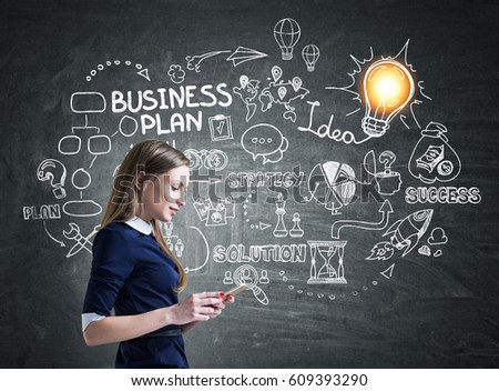 Side view of a young businesswoman in a dress standing near a backboard with a business plan drawning.