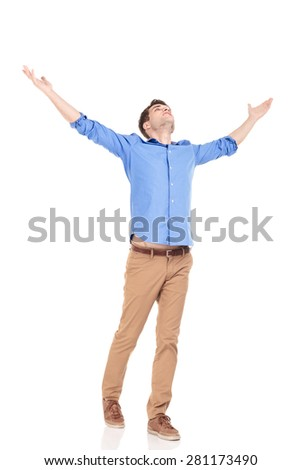 Side view of a young casual man holding both hands up celebrating. - stock photo