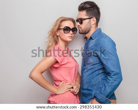 Side view of a young casual man looking at his girlfriend while she is holding her hands on her waist. - stock photo