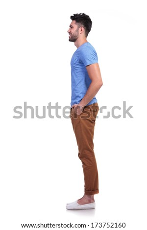 side view of a young casual man standing in line on white background - stock photo