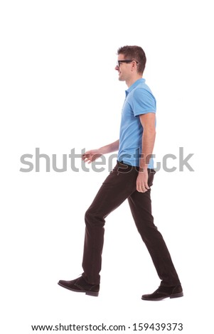 side view of a young casual man walking and looking forward. on white background