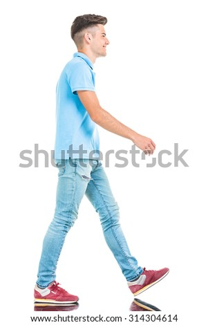 Side view of a young casual man walking on isolated background. - stock photo
