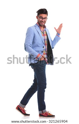 Side view of a young casual man walking with his hand in pocket while presenting something with his left hand. - stock photo