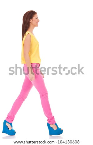 side view of a young casual woman walking on white background - stock photo
