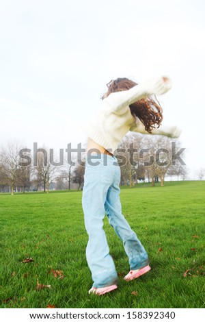 Side view of a young child girl jumping up against green grass and a blue sky while in a park with leafless trees, playing and being energetic during a sunny winter day, outdoors. - stock photo