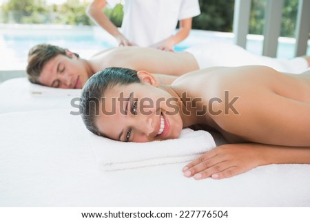 Side view of a young couple enjoying massage at health farm - stock photo
