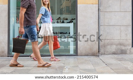 Side view of a young couple holding hands walking in shopping street with a shoe store window display, carrying shopping bags and spending money on holiday. Consumer lifestyle, outdoors. - stock photo