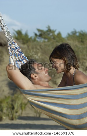 Side view of a young couple in hammock smiling - stock photo