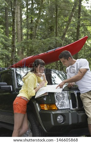 Side view of a young couple looking at map on car bonnet in the forest