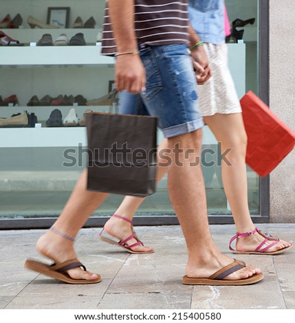 Side view of a young couple lower body section walking down a shopping street with a shoe store window display, carrying shopping bags and spending money on holiday. Consumer lifestyle, outdoors. - stock photo