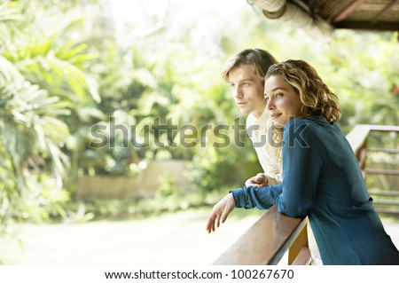 Side view of a young couple on vacations, leaning on a balcony's veranda and looking at a tropical garden.