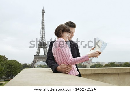 Side view of a young couple reading map on balcony in front of Eiffel Tower - stock photo