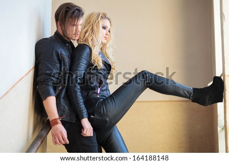 side view of a young couple standing against a wall and looking out the window - stock photo