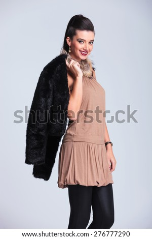 Side view of a young fashion woman smiling at the camera while holding her fur jacket on her shoulder. - stock photo