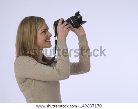 Side view of a young female photographer holding camera in the studio - stock photo
