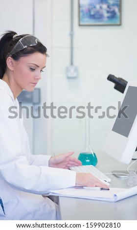 Side view of a young female researcher using computer in the laboratory - stock photo