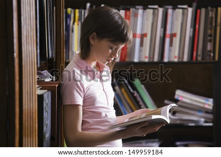 Side view of a young girl reading a book at the library - stock photo
