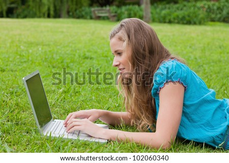 Side view of a young girl typing on her laptop while lying down in the countryside