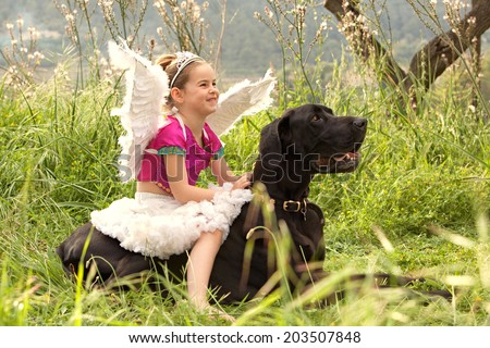 Side view of a young girl wearing a pink fancy dress with wings, sitting on her dogs back enjoying a sunny holiday in a green park field, smiling outdoors. Active family with animal pets, lifestyle. - stock photo