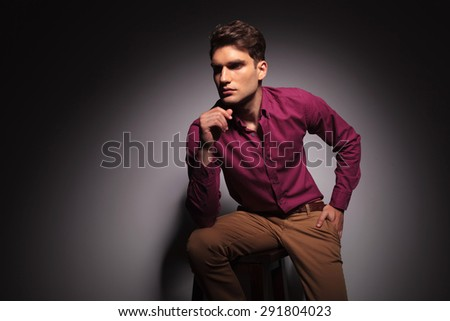 Side view of a young handsome man sitting on a stool with one hand in his pocket.