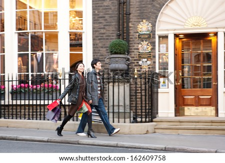 Side view of a young Japanese tourist couple on holiday walking down an exclusive and luxurious shopping street in London city with classic stores and holding carrier paper bags, outdoors. - stock photo