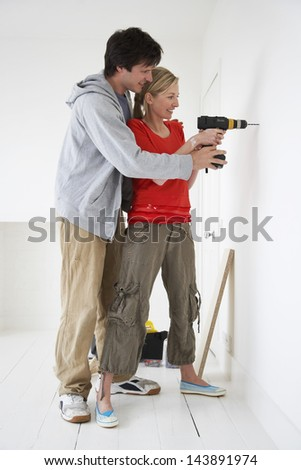 Side view of a young man and woman drilling hole in wall at their new home - stock photo