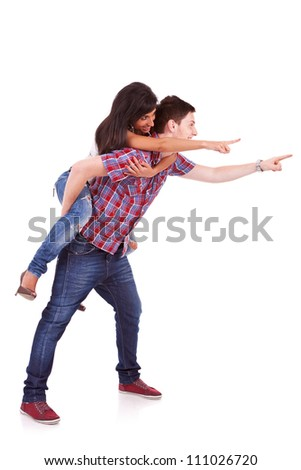 Side view of a young man carrying his girlfriend on his back with their hands pointing towards something