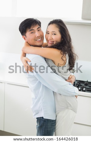 Side view of a young man embracing woman in the kitchen at home - stock photo