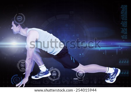Side view of a young man in ready to run posture against blue dots on black background - stock photo
